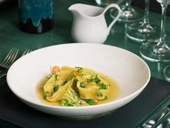 Tortellini with scallops, beans, herbs in seafood consommé